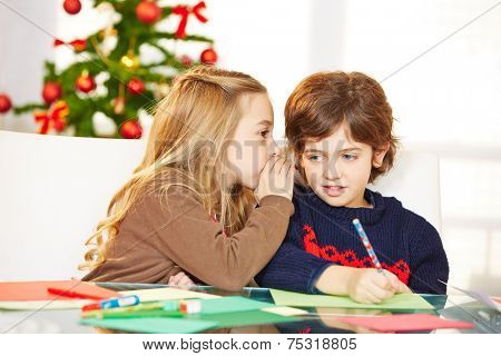Girl whispering a wish in the ear of a boy at christmas
