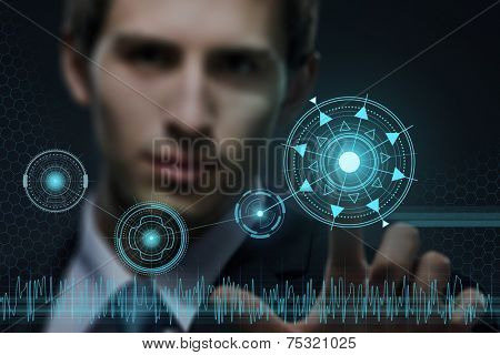 Young businessman working with modern virtual technology pressing keys on touch screen on black background