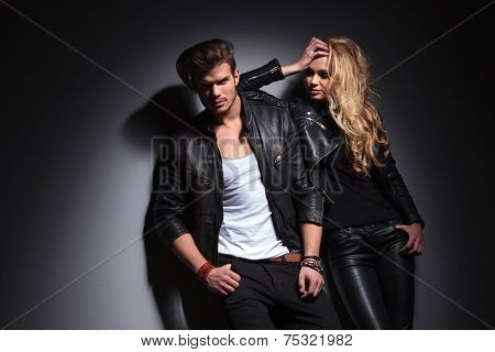 Fashion couple posing on grey studio background, the man si looking at the camera while the woman is leaning on him, looking down.