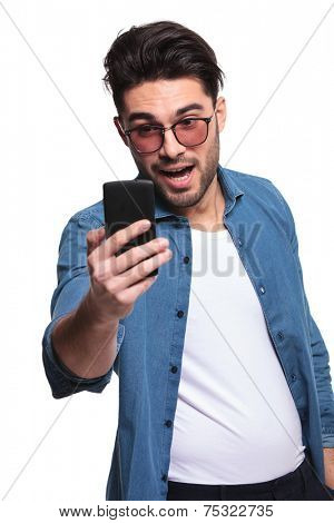 young casual man looking shocked by the good news he is reading on his phone.