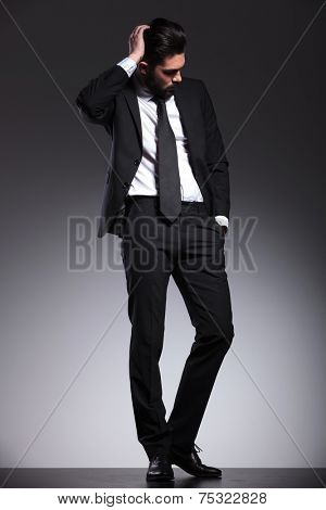 Full length picture of a young business man fixing his hair while looking down.