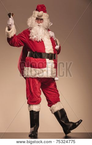 Full body picture of Santa Claus ringing a bell and holding a big red bag on his shoulder.