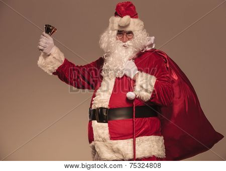 Santa Claus holding a his big bag on his shoulder and a bell in his hand, side view.