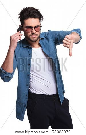 Casual young man showing the thumbs down gesture while talking on the phone.