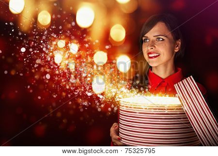 Beautiful girl opens magic box on bright background