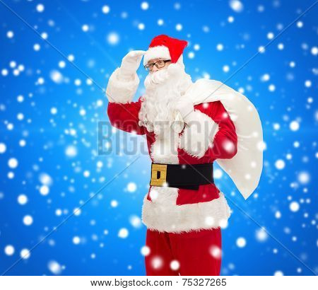 christmas, holidays and people concept - man in costume of santa claus with bag looking far away over blue snowy background