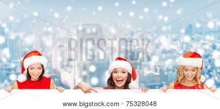 christmas, x-mas, people, advertisement and sale concept - happy women in santa helper hat with blank white board over snowy city background