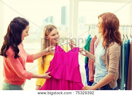shopping, fashion and friendship concept - three smiling friends trying on some clothes at home or shopping mall