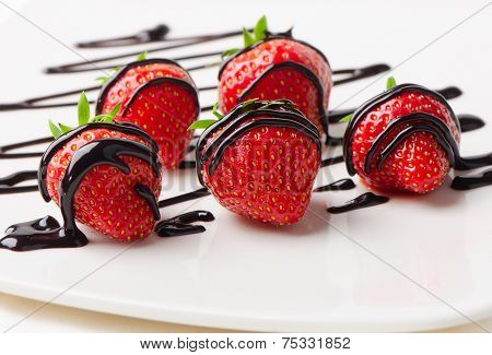 Strawberries Dipped In Chocolate Sauce On A  White Plate.