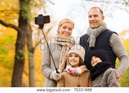 family, childhood, season, technology and people concept - happy family photographing with smartphone and selfie stick in autumn park