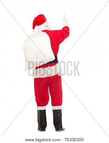 christmas, holidays and people concept - man in costume of santa claus with bag pointing finger from back