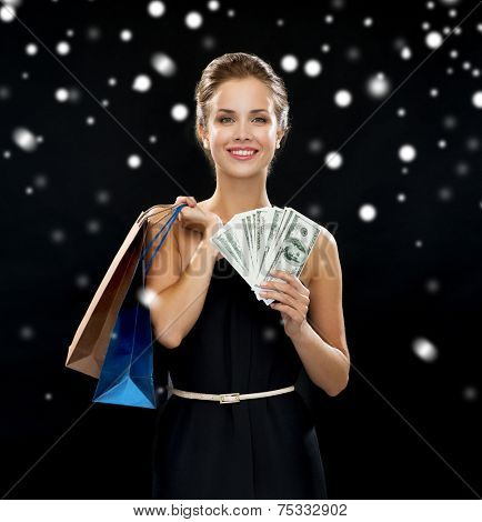 people, sale, money and holidays concept - smiling woman in dress with shopping bags and money over black snowy background