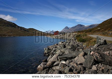 Scenic view of the Bygdin Lake with a red Norwegian holyday house, Jotunheim Mountains