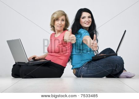Two Smiling Women Sitting On Floor With Laptops