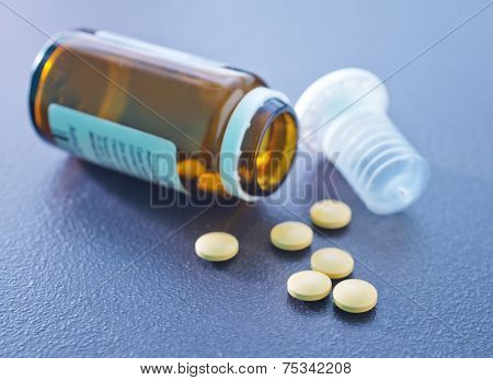yellow pills on the black table