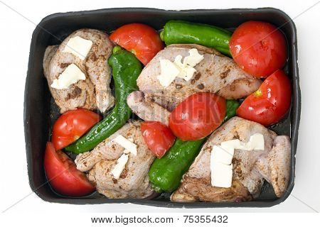 Spice rubbed  chicken ready for roasting in a tray with tomatoes,  long sweet lebanese peppers and chicken stock