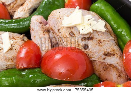 cut-up chicken, marinaded with spices in a roasting tin with vegetables, stock and a knob of butter,