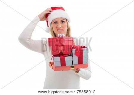 Confused blonde in santa hat holding gifts on white background
