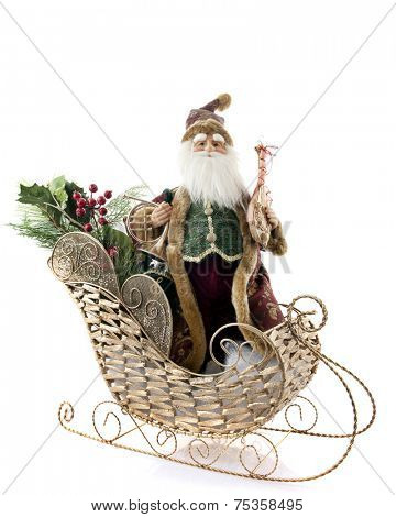 An old-fashioned santa figurine in a gold wire sleigh with berries and greenery.  Isolated on white.