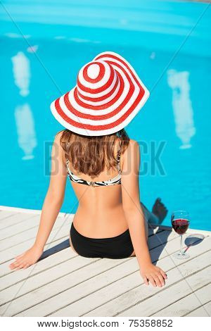 Back shot of young woman sitting close by swimming pool