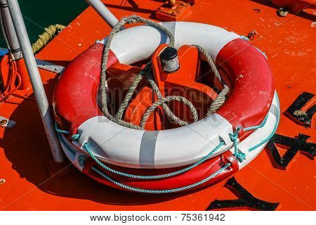 Close-up Of A Red And White Weatherd Life-belt (buoyancy Aid) On The Deck Of A Fishing Boat.