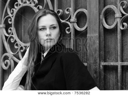 Beautiful Girl Pats Her Hair By The Forged Gates, Grayscale