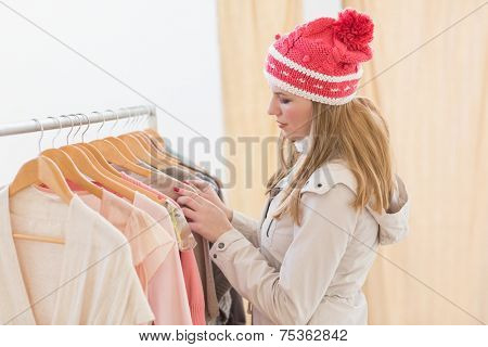 Pretty blonde looking at clothes on rail in the store