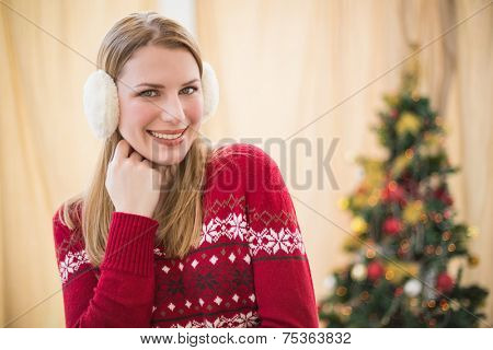 Portrait of a pretty smiling blonde wearing earmuffs at home in the living room