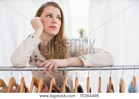 Pretty blonde thinking through clothes rail in the store