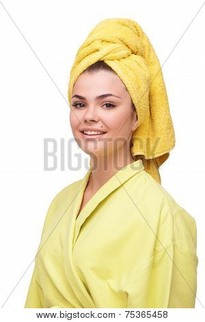 Smiling young woman in bathrobe and towel
