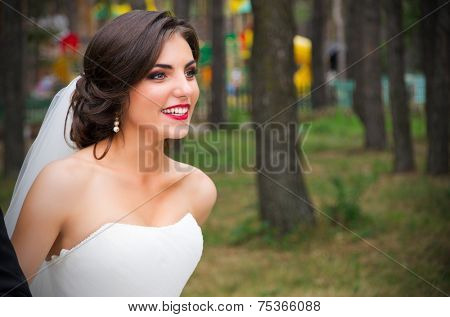 Happy young bride at forest