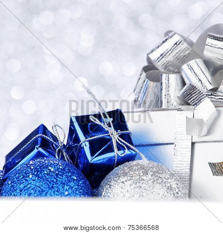 Decorative Christmas balls and gifts on abstract glitter silver background