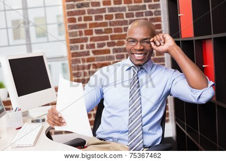 Portrait of smiling young businessman with document in office