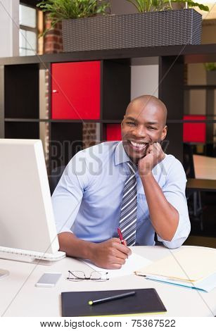 Portrait of young businessman with computer sitting at office desk