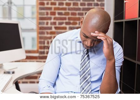 Young businessman sitting with head in hand in the office