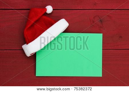 Blank green Christmas envelope sign with Santa Claus hat against antique red wooden background