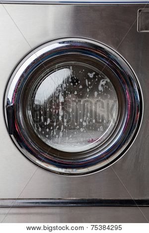Closeup of washing machine with foam on front load