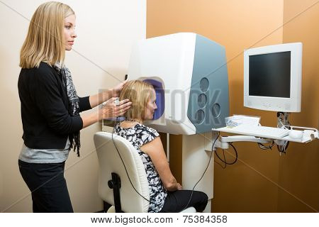 Female optometrist adjusting patient's head while looking at computer for retinal checkup