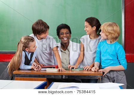Portrait of young teacher sitting at desk with students looking at her in classroom