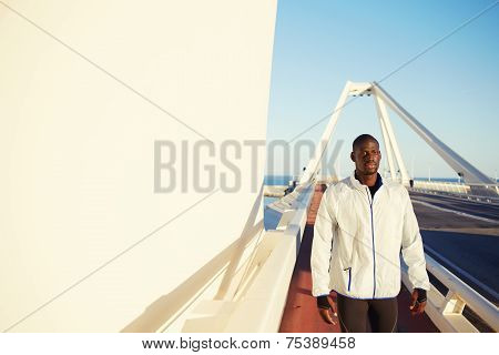 Dark skinned runner in windbreaker resting after workout standing on modes bridge