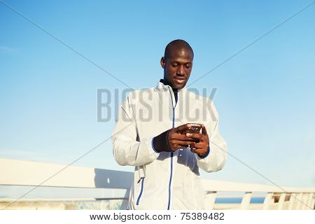 Runner using mobile smartphone standing at sunset on the road