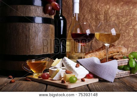 Supper consisting of Camembert and Brie cheese, wine and grapes on cutting board and wine barrel on wooden table on brown background