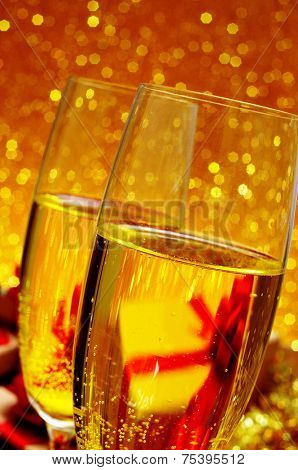 closeup of two glasses with champagne on a festive and shiny golden background