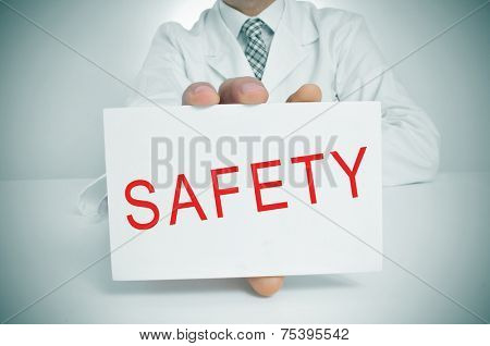 closeup of a doctor showing a signboard with the word safety written in it