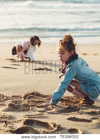Two Little Girls Squatting And Playing In The Beach