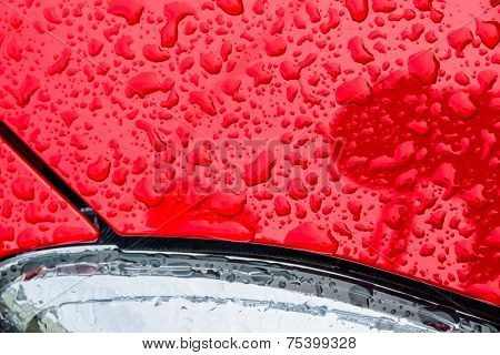 after a rain, droplets of rain on the paint from a car. water drops on red background