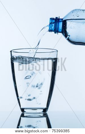 from a bottle of water being poured into a glass, symbol photo for drinking water needs and consumption