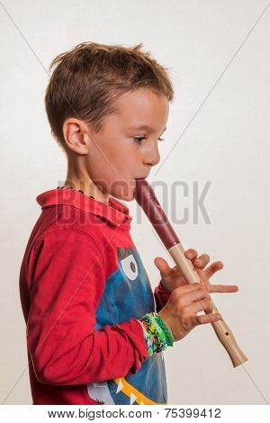 a child playing on a flute on wood. music education and music school.