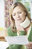 pic of neck brace  - Woman Reading Letter After Receiving Neck Injury - JPG