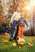 stock photo of heartwarming  - Father with son playing in football at the autumn park - JPG